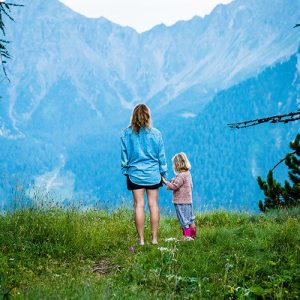A mother stands with daughter as both look out at the mountains in front of them. A vast valley lays between them and the mountains. This symbolizes the feelings of emptiness and isolation that may come with postpartum depression. We offer prostpartum depression counseling in Phoenix, AZ, trauma counseling, and more.