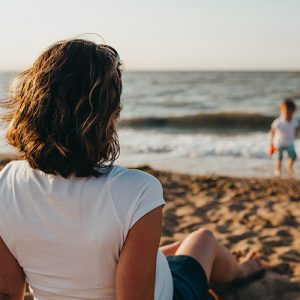 A close up of a woman sitting alone on the beach. This symbolizes the isolation one may feel from depression. Ataraxis Counseling offers therapy for depression in Phoenix, AZ. Contact us for online therapy, postpartum depression counseling, and more.
