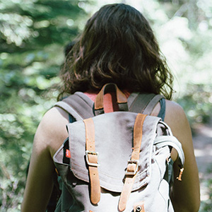 A woman wearing a backpack walks down a forest path. They are walking alone, with their back to the camera. This symbolizes how cut off one may feel from others due to their anxiety symptoms. An anxiety therapist in Phoenix, AZ can offer support with anxiety treatment. Contact us today for online therapy to support.