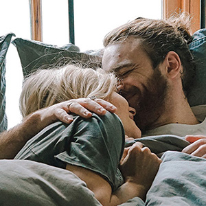 A couple smile as they kiss and cuddle in bed. This symbolizes the intimacy and love a couple may feel after sex therapy in Phoenix, AZ. Ataraxis Counseling offers marriage counseling, online therapy, sex therapy, and more. Contact a couples counselor for support.