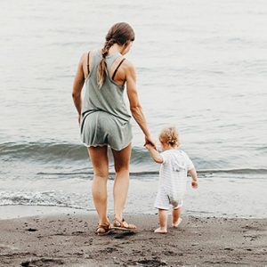 A mother walks with her young child in hand on the shore. The muted colors suggest a hollow, empty feeling. This symbolizes postpartum depression symptoms one may experience. We offer postpartum depression counseling, trauma counseling, and more.