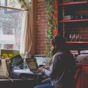 A woman sits at a coffee shop table while typing on her laptop. This symbolizes the kind of environment one may start start an online therapy session. We offer online therapy in Phoenix, AZ, online marriage counseling, and more. Contact a couples counselor for support.