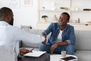 African American man shakes hands with his therapist. He is happy with the results from career counseling in Phoenix, AZ. Ataraxis Counseling offers career counseling in Phoenix, AZ. Contact us for men's counseling, relationship counseling for men, and more.