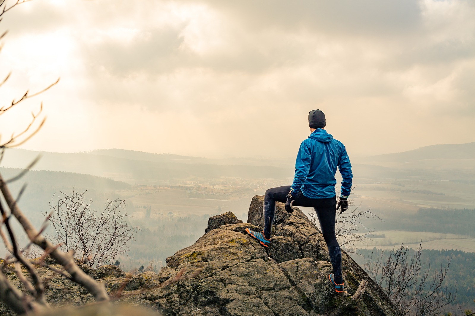 Man poses on summit of a large rock formation. He is feeling full of energy thanks to performance counseling in Phoenix, AZ. Ataraxis Counseling offers counseling for dads, performance counseling, relationship counseling for men, and more.