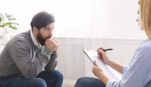 A man is hunched over as he listens to his therapist. He is there for counseling for fathers in Phoenix, AZ. Ataraxis Counseling offers men's counseling in Phoenix, AZ. Contact us for relationship counseling for men, marriage counseling for men, career counseling, and more.
